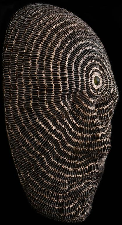 Rows of polished screws define the contours of a large face merging into concentric circles around a glass stone at the forehead. The title of this contemplative bronze and steel wall sculpture refers to the third eye or 6th chakra in the Hindu