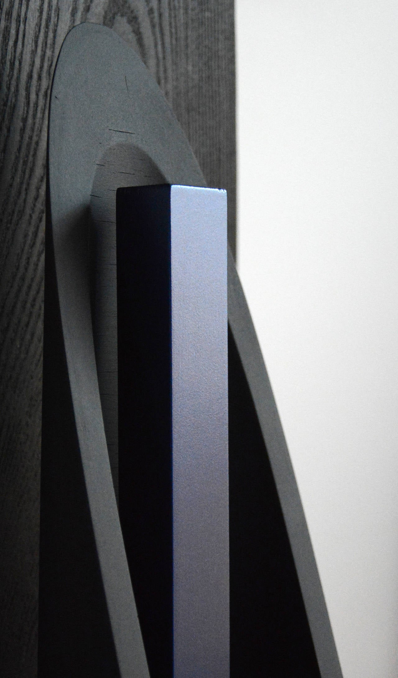 This sculpture is created with carved and charred, burnished wood. The black  matte finish of the taller elements exist in sharp contrast with the high gloss blue enamel finish of the central figure.  Sculptor Edward Falkenberg, RCA, attended the