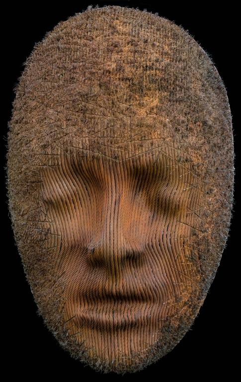 A large scale hanging mask, made of steel aircraft cable. The artist has distressed and roughed up the steel around the perimeter of the face, fraying the ends of the cable strands. Sensuous, powerful and sophisticated sculpture.  Sculptor Dale