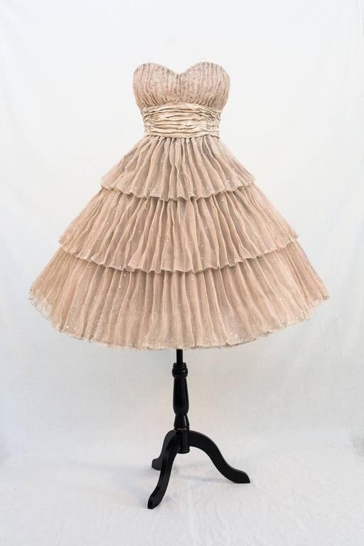 """Elegant 1950's style cocktail dress, recalling the glamour of Marilyn Munroe and Grace Kelly, mounted on a stand like a dress-maker's """"judy"""".  Toronto-based artist, Sophie DeFrancesca graduated from the Ontario College of Art (now OCAD University)"""