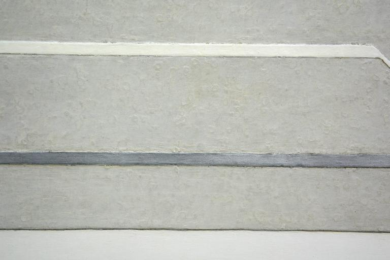 White, grey and silver abstract horizontal three dimensional wall painting.   Maki's work is influenced by early Modernist Abstraction, while her combination of materials and technique make the pieces uniquely her own. This work, in subtle shades