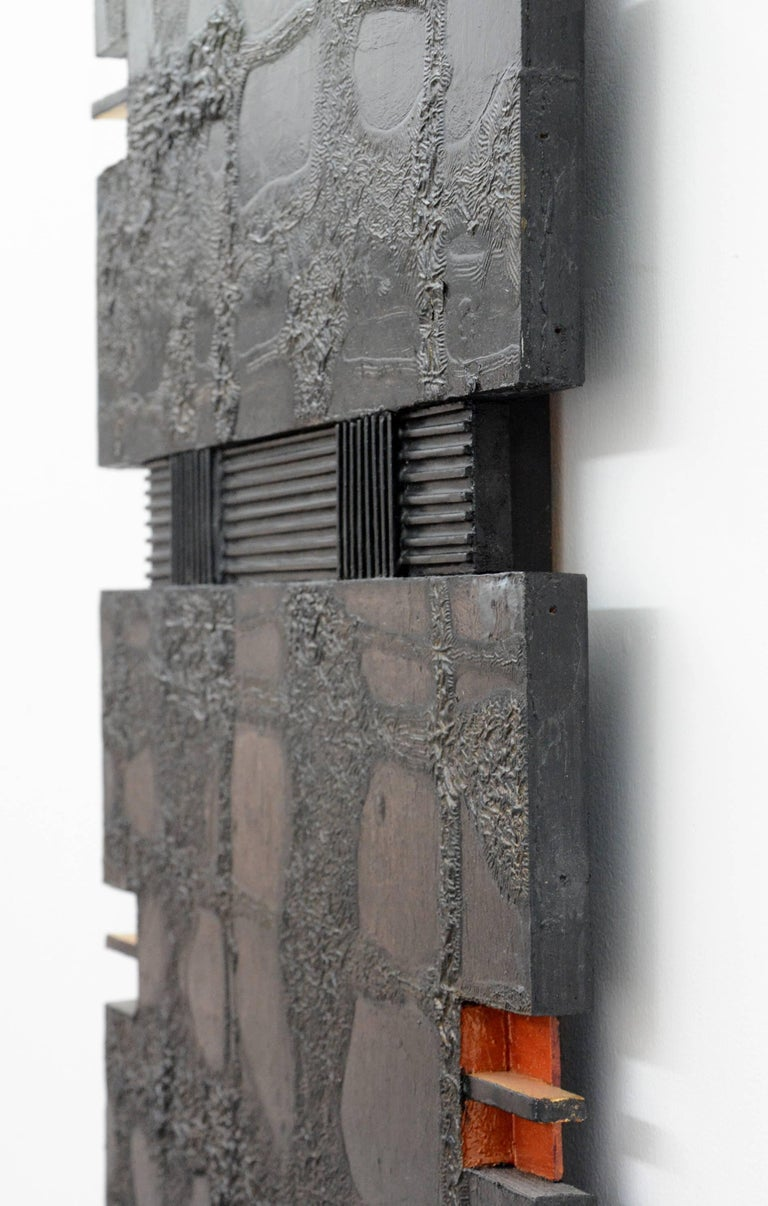 Two textured, brown and black patinated, wood sections each with two orange cutouts intersect with a ribbed black vertical in this 30 inches tall wall relief.