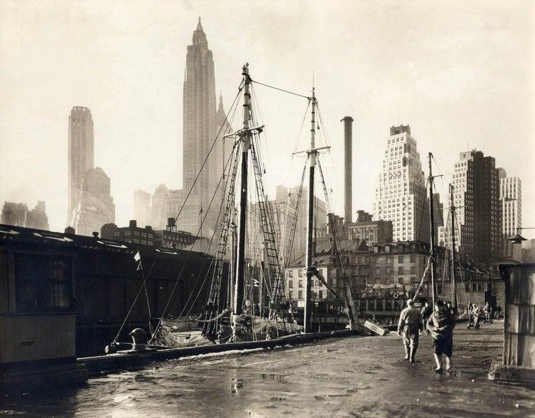 Berenice Abbott Black and White Photograph - Fulton Street Market, Manhattan Skyline