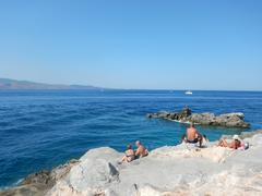 Sunbathers on the rocks at Spilia, Hydra, Greece