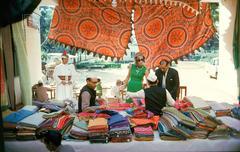 Tiger Morse Examines Saris, Benares, 1962