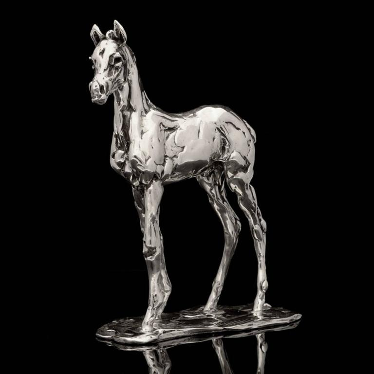A 'Standing Foal' sterling silver sculpture by Lucy Kinsella, the limited edition finely modelled foal has been sculpted in Kinsella's instantly recognisable dynamic style and demonstrates her skill at conveying personality in the animals she