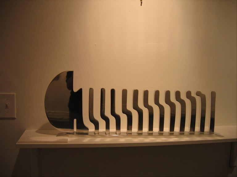 Marked by precision in form and elegant simplicity, this is a polished aluminum sculpture. The sculpture has great movement and rhythm. It is signed by the artist on the right. It is sold with its own customized wooden case.  Martin Rubio is a New