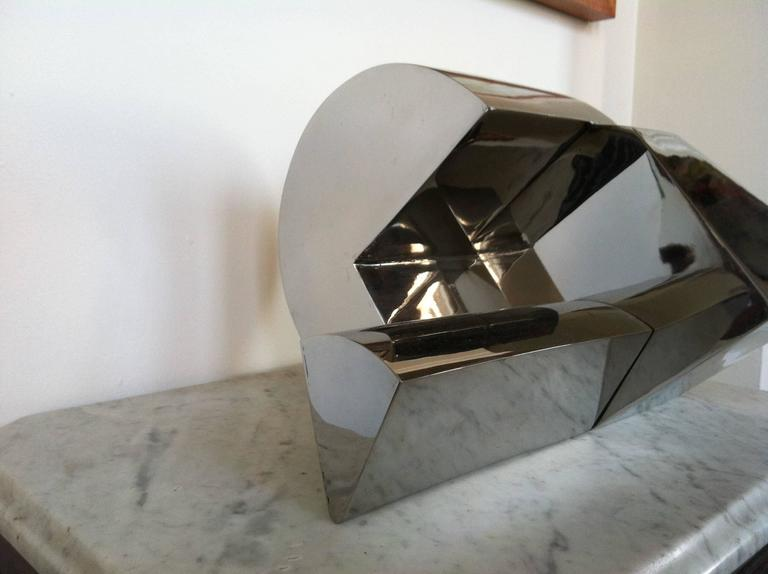 This elegant stainless steel sculpture relies on forms that change according to the angles at which the piece is observed. It rests on three points that change as the piece is moved. The sculpture represents a fine example of simplicity finely