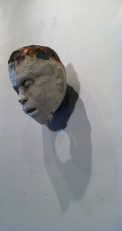 This head , a ceramic sculpture in earth tones, is realized in a primitivist mode. The face of the sculpture is pale white topped by earth tones in darker shades; it is reminiscent of indigenous people for whom the soul inhabits the visage. The