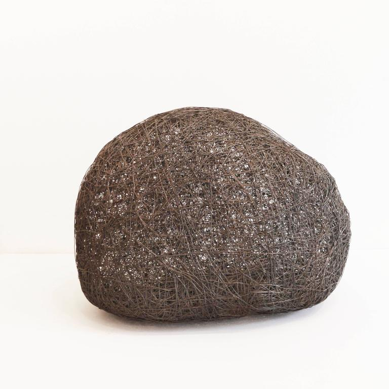 """Stones: immutability, eternity, abstract shape. With hundreds of meters of iron wire woven in """"Sasso"""" (Stone) is a sculpture that has the shape of a solid weighty object, but which traps light and emptiness within its layered and textured"""