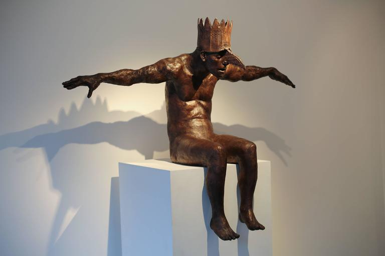 This modern contemporary figurative sculpture, is a bronze casting of human figure with crown with a fantasy quality. The arms are spread like wings with a human head and bird beak, slouched and seated, forward reaching posture.  Anyone who shares