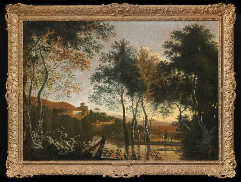 An Italianate landscape with a figure and his dog by a lake, a hill-town beyond