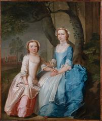 A portrait of two sisters sitting on a wooded bank with a view of a country hous