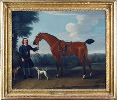A saddled bay hunter held by a liveried groom and two harriers in a wooded lands
