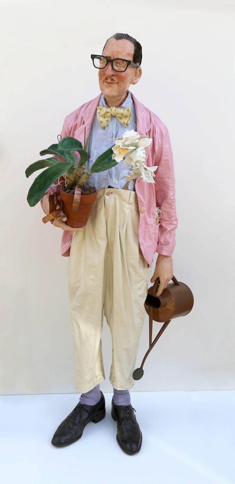 Artist: Kay Ritter Title: Florist Medium: Papier-mache with metal watering can, glasses, papier-mache flowers Year: 1995 Size: 57  x 24  x 14 in. (144.78  x 60.96  x 35.56 cm)