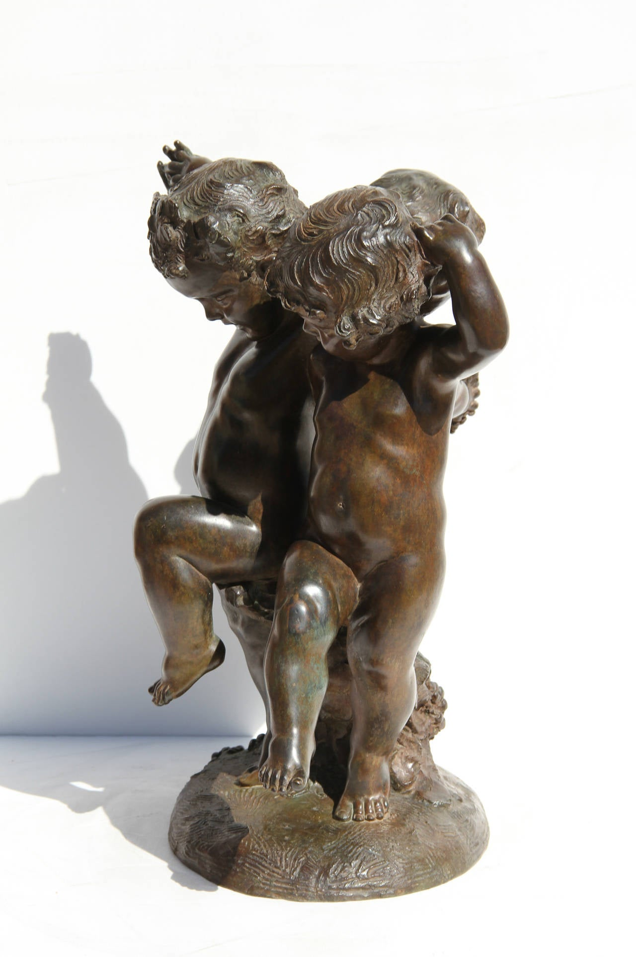 This Bronze sculpture, by the French artist Affortunato Gory, is a beautiful moment of three putti joyously dancing together.  Their arms are joined as they dance and hold grapes.  Signature inscribed.