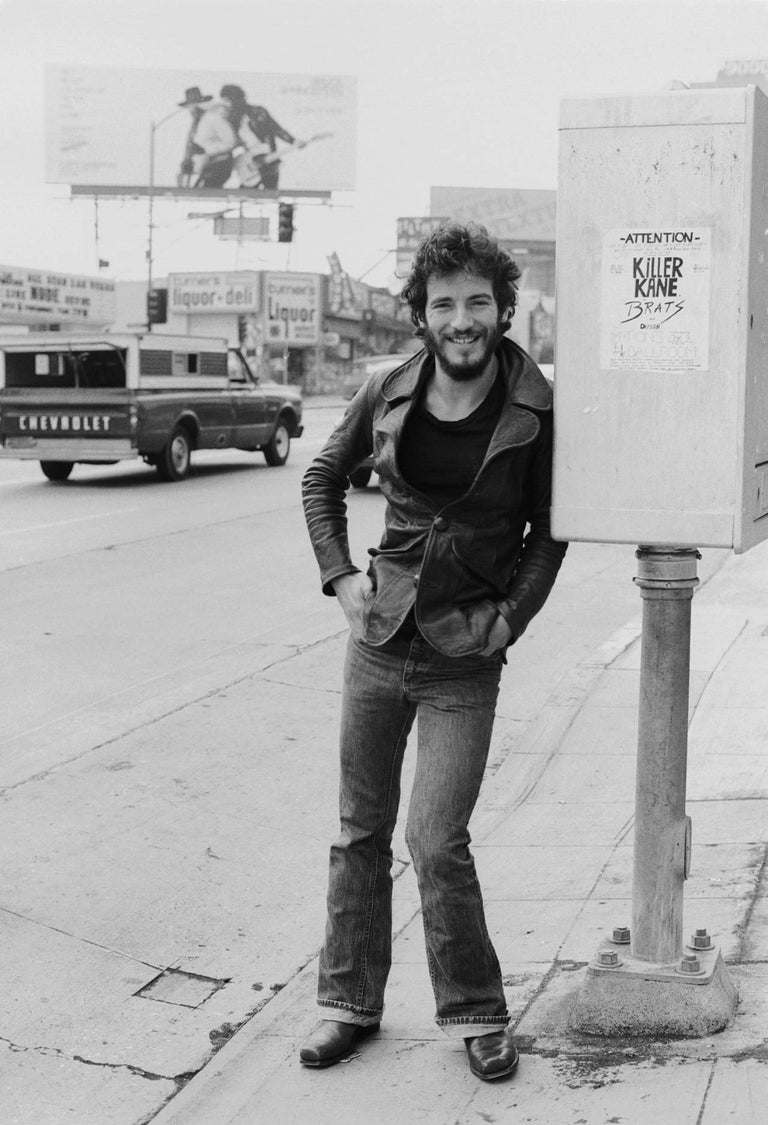 Terry O'Neill Black and White Photograph - Bruce Springsteen, Hollywood Boulevard, in front of  Born To Run Billboard