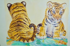 Two Tiger Cubs, seated on the ground.