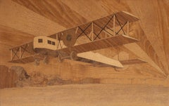 An art deco inlaid panel depicting a biplane off the coast