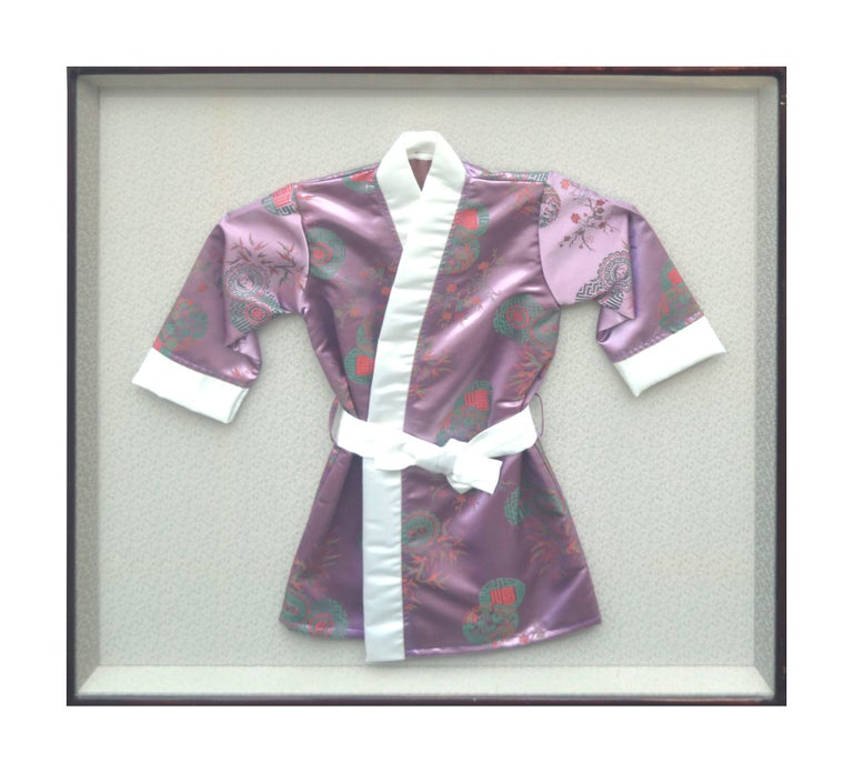 """Beautiful and charming, this woven silk child's kimono robe in frame makes a wonderful accent. Circa 1970. Presented in wooden frame under glass with ornate brass hanger. Image size: 30""""H x 30""""W. FRAMED"""
