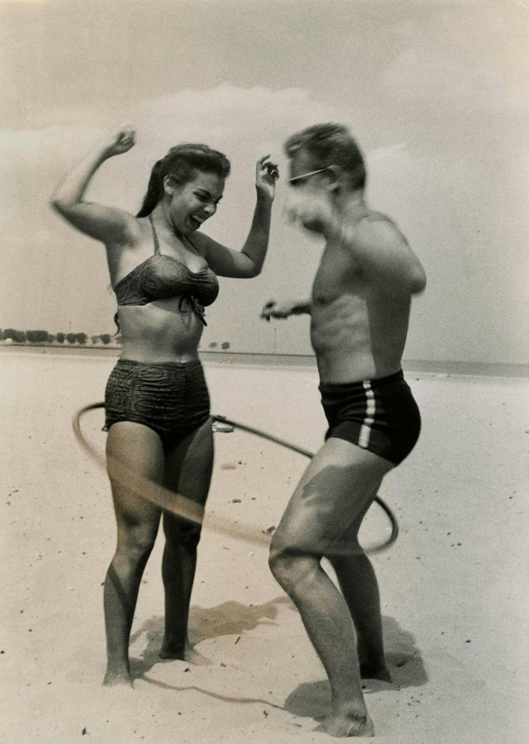 This 1958 Vintage Silver Gelatin Print by Art Shay shows a couple on the beach sharing the iconic toy of the time - the Hula Hoop.  Art has captured their timeless joy, expressed in their faces.  The print is framed with a simple black metal frame