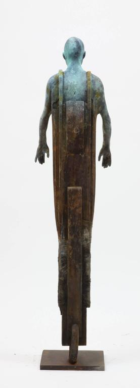 This cast bronze sculpture of a figure whose body is incorporated and bound together inside a cocoon of geometric and organic shapes.  His foot has transformed into a wheel.  The combination of matte rust and verdigris bronze emphasize the depth of