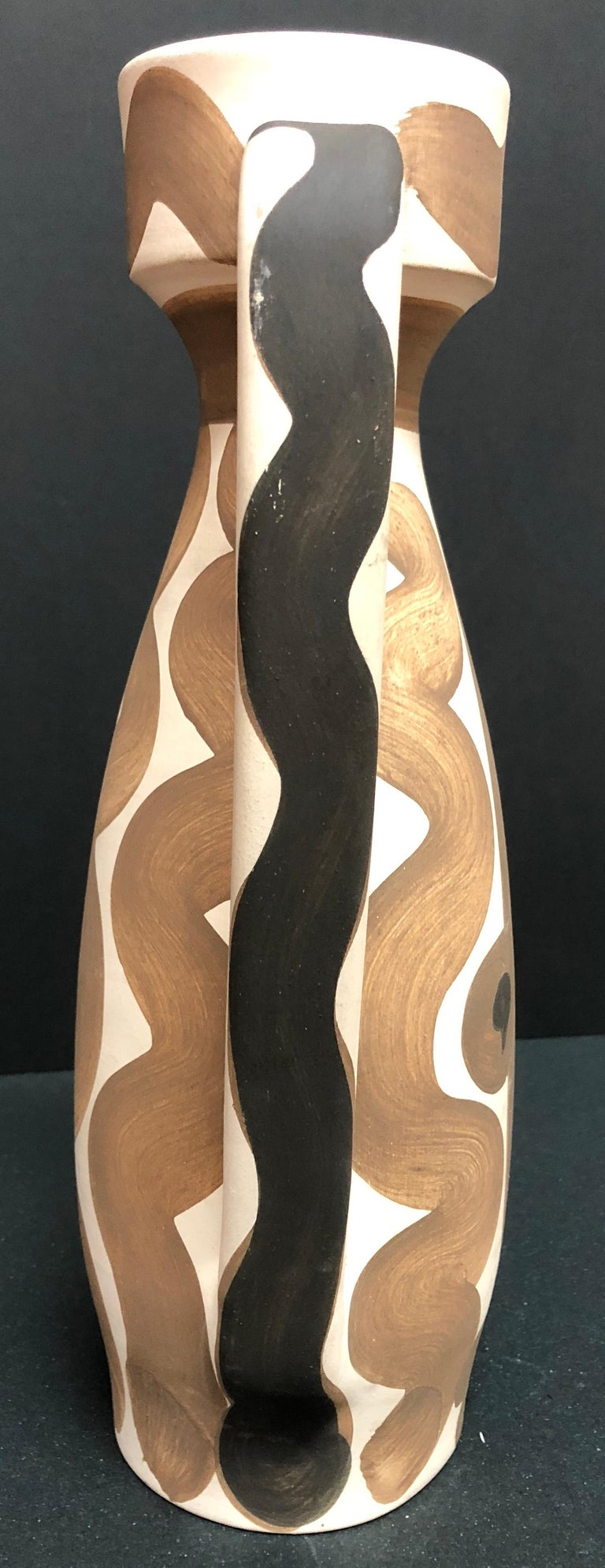 This piece is an A.R. turned pitcher created by Pablo Picasso in 1955.  It is made with white earthenware clay, decoration in engobes in red and black with glaze inside. It bears the