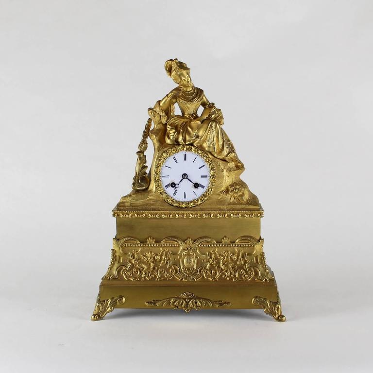 French ormolu clock circa 1860, depicting a lady in court dress reading a book, with French chiming movement