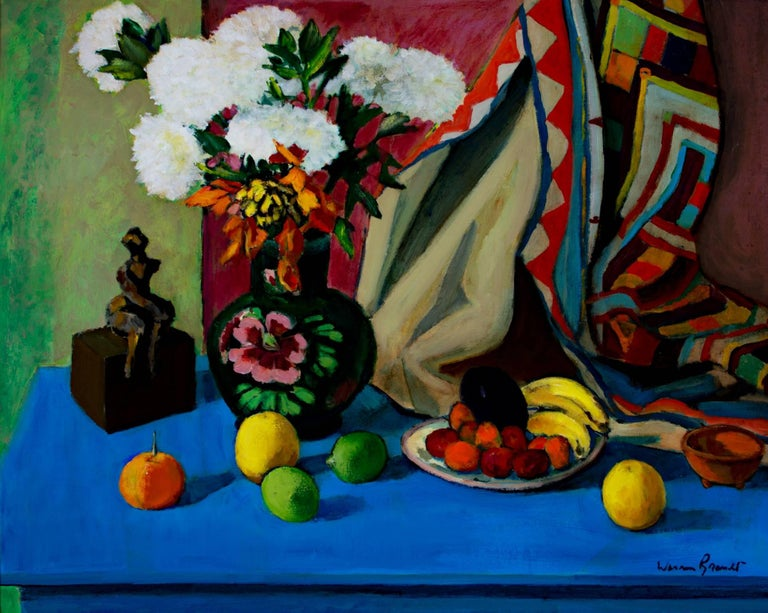 """Rich, colorful, expressionist still life by American artist Warren Brandt featuring a decorative vase with white flowers, an assortment of fruit, and a small wooden sculpture against a bright blue table.   24"""" x 30"""" art 29 1/2"""" x 35 5/8"""""""