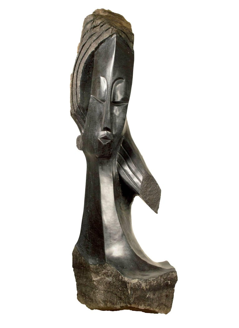 """""""My New Hairstyle"""" is an original signed springstone sculpture by the Shona artist Witness Bonjesi. It depicts an elongated female face with textured hair and weighs 150 lbs.   40"""" x 14"""" x 11"""" art  Witness Bonjisi was born September 25th, 1976 in"""