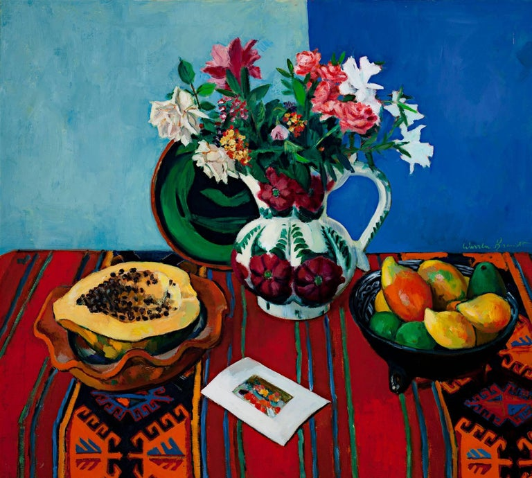 """""""Papaya & Mexican Pitcher"""" is an original signed oil painting by Warren Brandt. The piece depicts a still life of fruit and flowers in decorative pottery. Each piece sits on a bold red tablecloth in front of a blue background.   26"""" x 29"""" art 26"""