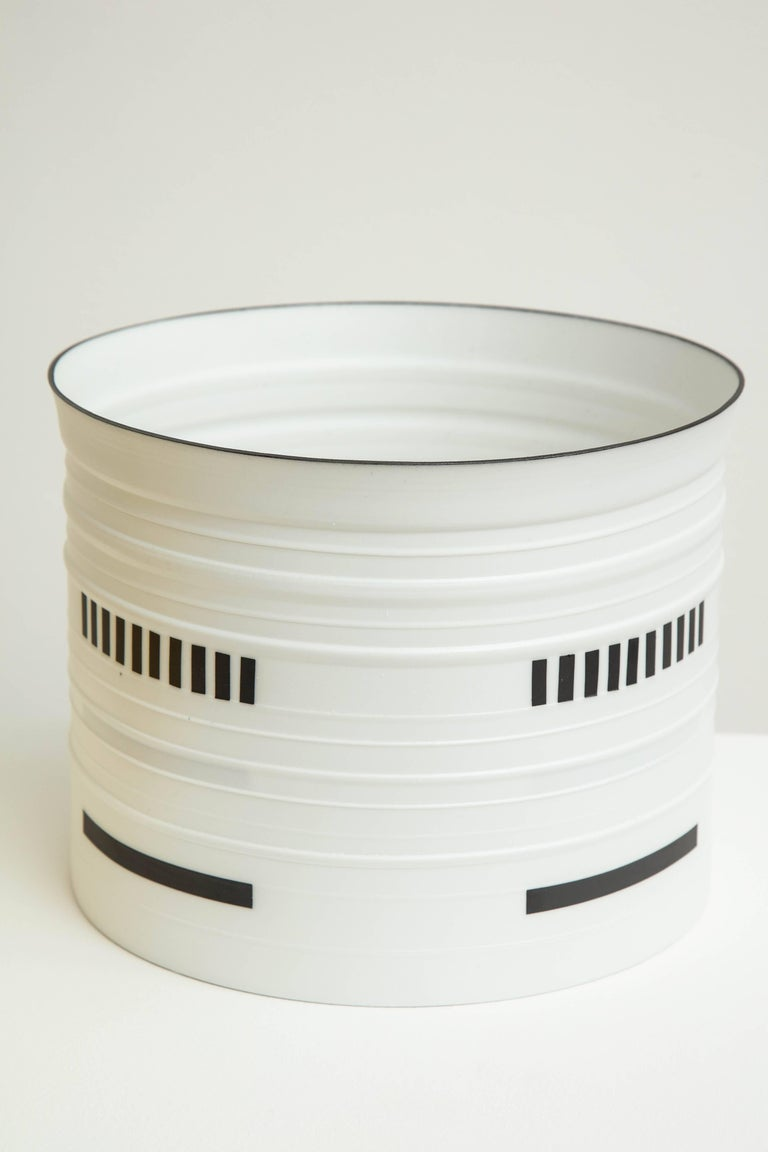 Bodil Manz is a ceramicist known for her use of ultra-thin, translucent eggshell porcelain to create distinctive cylindrical forms, anchored by bold, geometric abstractions in a style evocative of Russian Suprematism. Manz was born in Copenhagen in