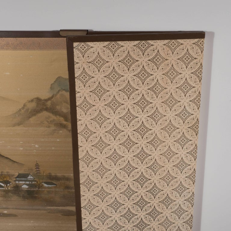 This gorgeous Art Deco screen was realized in Japan, circa 1925. Consisting of four rectangular panels of equal size, this screen features a cloudy mountain scape with a quaint village nestled in the center, as well as a craggy cliff with