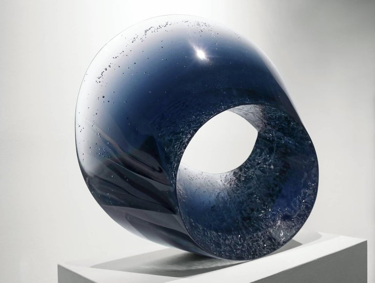 """This gravity-defying pedestal sculpture is stunning from all angles, with the color and transparency constantly changing as the lighting shifts or as you walk around the different sides. The cast glass sculpture """"Skyfall II"""" reflects sculptor Josef"""