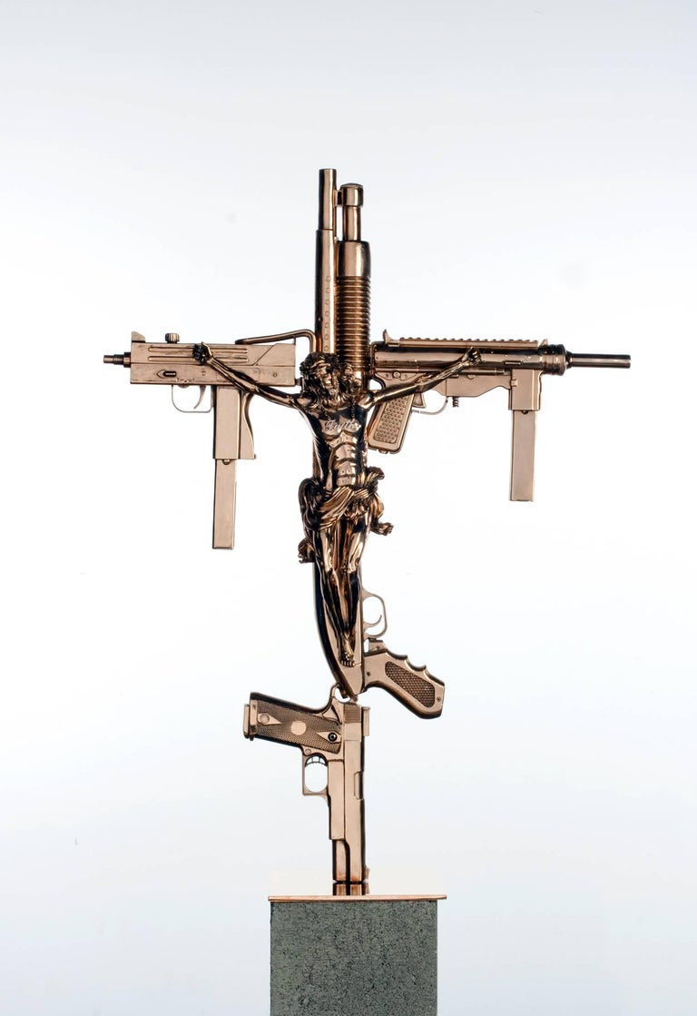 "Contemporary sculpture comprised of cast bronze guns and crystal stones in the form of a crucifix.   ""Crucifix,"" 2012 Polished cast bronze, crystal stones.  Edition of five (5) plus one (1) AP. Signed and numbered to base.  35 x 25 x 25 in."