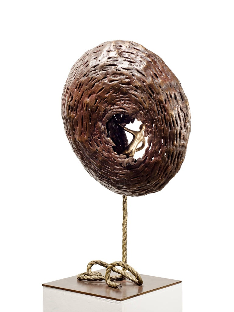 From The Soul is a bronze sculpture by Beatriz Gerenstein where she shows a golden-brown, chrysalis-like structure with and a human figure looking outwards from an opening in the nest.  The whole sculpture seems to be floating. It is light and heavy