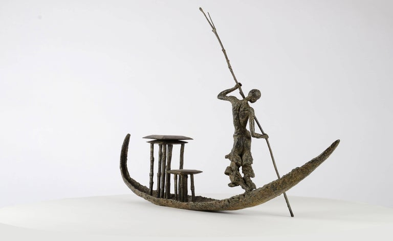 D'une Rive à l'Autre is a bronze sculpture by French contemporary sculptor Marine de Soos. It represents a standing half-naked woman paddling a dugout canoe. From Africa to the Orient, Marine de Soos relates true stories and conveys moments of pure