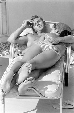 Steve McQueen and his wife, Neile Adams, laying on a chair, California, 1963