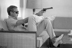 Steve McQueen aims a pistol in his living room, California, 1963