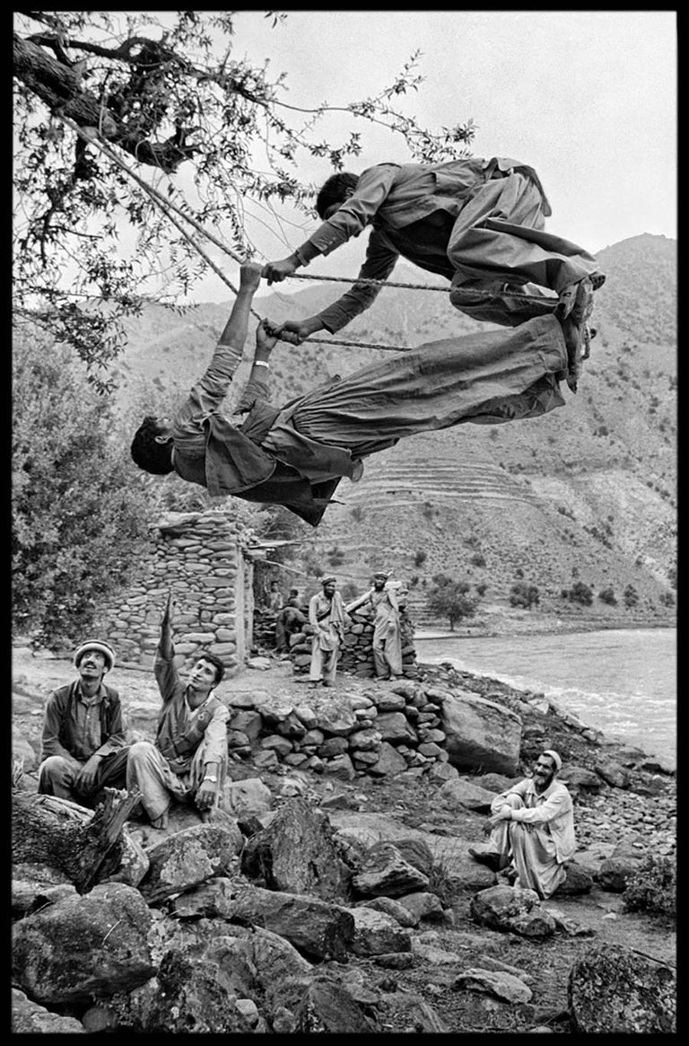 Steve McCurry Figurative Photograph - Young Mujahideen on Swing, 1980