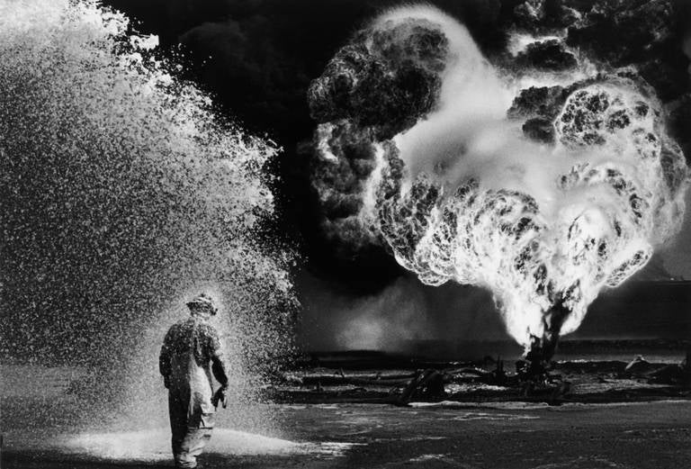 Desert Hell, Kuwait, 1991 - Black and White Photography Sebastião Salgado Stamped with photographer's copyright blind stamp Signed, inscribed on reverse Silver gelatin print 20 x 24 inches  Undertaking projects of vast temporal and geographic scope,