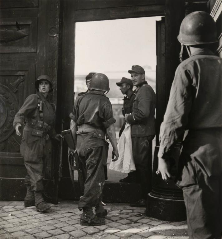 Robert Capa Black and White Photograph - Captured German Officer with Allied Soldiers During Paris Liberation
