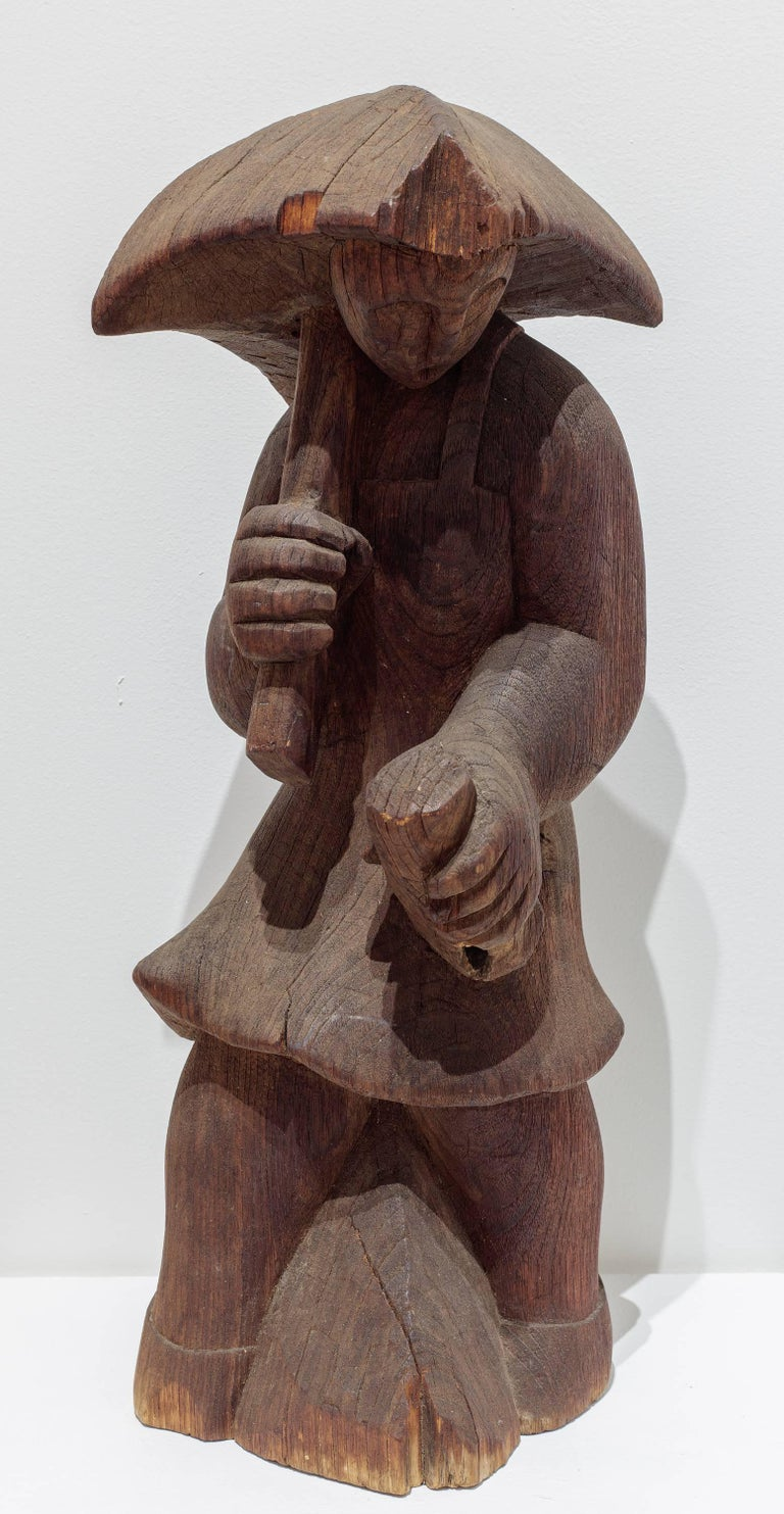 """A sculpture in wood depicting a woman holding an umbrella. """"Woman with Square Umbrella"""" by Post War artist Alexander Calder is signed underneath, """"Calder."""" """"Woman with a Square Umbrella"""" is an early example of Calder's wood carvings and particularly"""