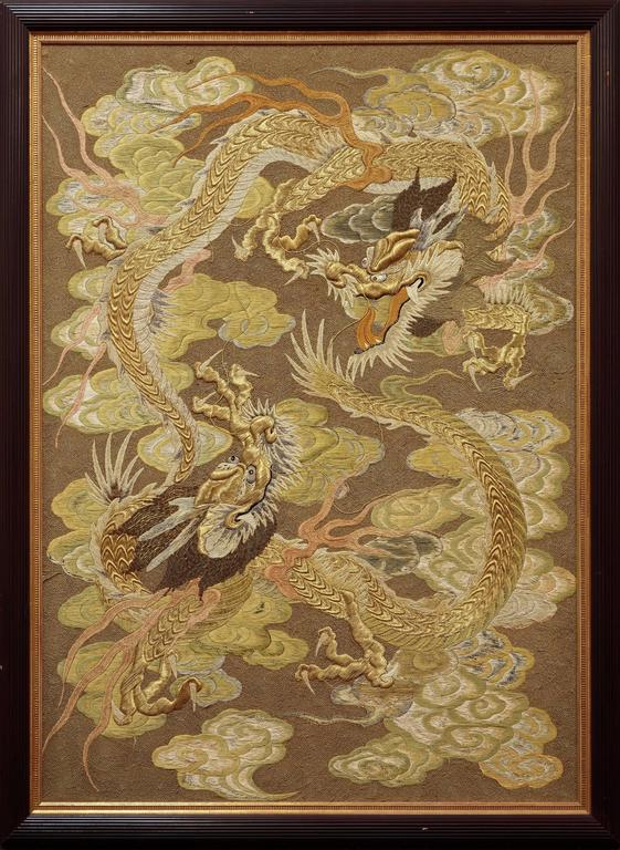 A Japanese Embroidery. Create by artists unknown, this Japanese, silk thread embroidery is executed in an earth toned palette and depicts a pair of circling dragons amidst swirling clouds. Japanese, Late 19th Century