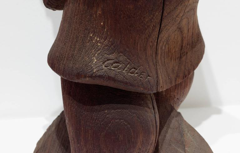 A sculpture in wood depicting a woman holding an umbrella.