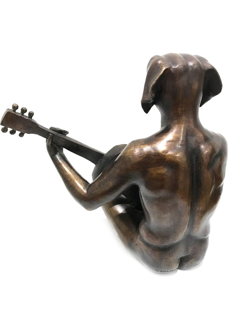A whimsical yet very strong piece depicting the Dog Man from Gillie and Marc's iconic figures of the Dog/Bunny Human Hybrid, which has picked up much esteem across the globe. Here we find Dog Man seated while playing the guitar. The artists want to