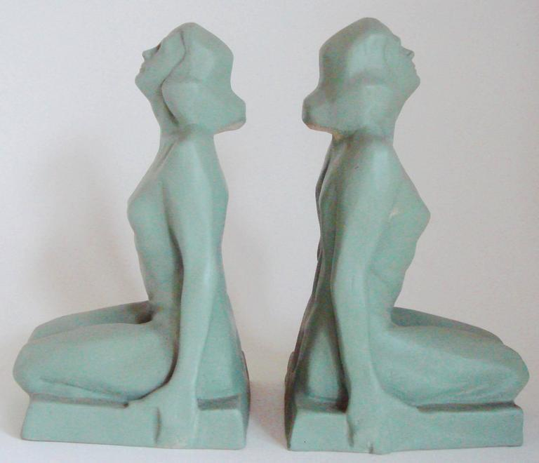 This stylish pair of hollow-cast American Art Deco female nude figural bookends are beautifully sculpted and painted in a soft Lovat green. They are in excellent condition with one being signed B.Foley to the underside of the base.