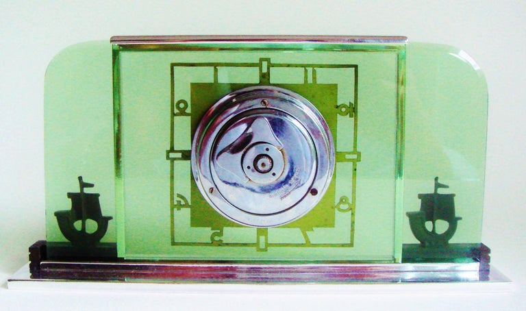 This very elegant, high end German Art Deco 8-day, six jewel, figural desk/ table clock features a chrome bezel, base and movement housing. The body of the clock is a sheet of beveled green glass with radius cut corners. This sets off a stencil cut