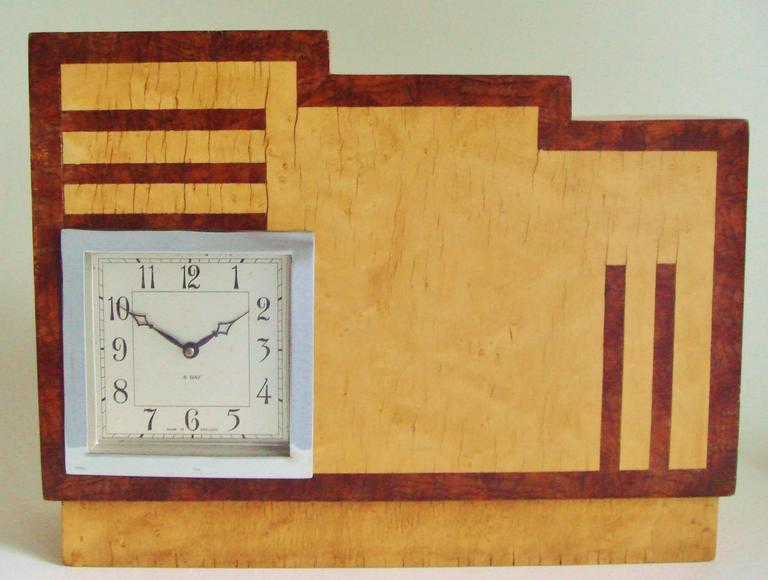 This extremely architectural English Art Deco mechanical mantle clock features a geometric inlaid veneered pattern of blonde birds-eye maple contrasted with burl walnut. The body of the clock is cut from a laminated block of wood that is
