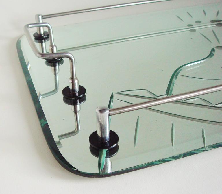 The deep etched mirror on this Australian Art Deco cocktail tray features a exuberantly rendered champagne bucket containing a bottle with the cork exploding out plus a flying martini glass and olive on a stick. The handles and gallery are plated in